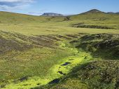 Lush Vivid Green Moss In Small Stream. Volcanic Landscape With Green Hills And Colorful Volcanos At  poster