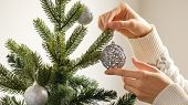 Decorate The Christmas Tree With Christmas Toy. Closeup Image Of Woman In Sweater Decorating Christm poster