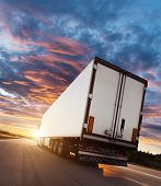 Backview of european truck vehicle on motorway with dramatic sunset light. Cargo transportation and  poster