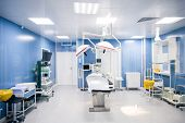 Interior of surgery room in modern clinics with all necessary equipment along walls and surgical tab poster