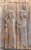 Bas-relief with assyrian warriors with spears on wall of tomb of Artaxerxes III, located on the slop poster