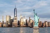 Statue of Liberty with background of New York city Manhattan skyline cityscape at sunset from New Je poster