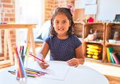 Beautiful toddler girl drawing cute draw using colored pencils at kindergarten poster