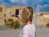 Young European Woman Taking Picture Of Sightseeing On Mobile Phone In European City During Her Vacat poster