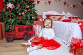 Little Girl With A Christmas Tree. Family Celebration. Smart Family Next To The Christmas Tree. New  poster