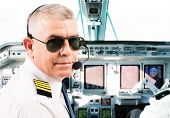 stock photo of cabin crew  - Airline pilot wearing uniform with epaulettes and headset working in airliner during flight - JPG