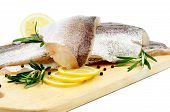 picture of hake  - Raw Fish Hake Fillets with Lemon Black Peppercorn and Rosemary on Cutting Board closeup on white background - JPG