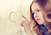 image of enamored  - sad enamored girl draws a heart on the window in the rain - JPG