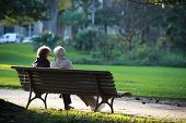 image of sitting a bench  - Two senior sat on a bench - JPG