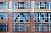 stock photo of derelict  - Broken windows on old derelict building with reflections - JPG