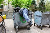 stock photo of dumpster  - A homeless man looking for food in a garbage dumpster - JPG