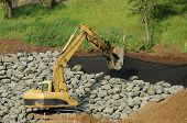 stock photo of rip-rap  - Exchavator Placing Rip Rap rock for steep bank stabilization for new building Roseburg OR - JPG
