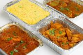 Indian takeaway food selection in foil containers.