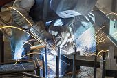 stock photo of welding  - Industrial worker welding steel in the dark