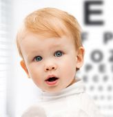 medicine, health and vision concept - adorable baby child with eyesight testing board