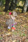 image of overcoats  - Pretty little girl with bows in overcoat disrupts red toadstool in forest - JPG