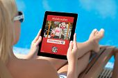picture of bathing  - girl in a bathing suit lying on a sun lounger by the pool with a computer tablet with mobile wallet onlain shopping on the screen - JPG