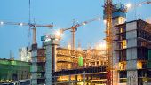 stock photo of hazard  - Big Construction Site Cranes at dusk - JPG