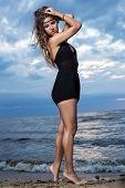 Woman in black dress is posing near the sea with bare feet