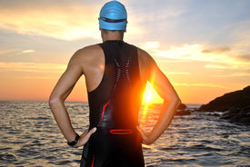 stock photo of triathlon  - young athlete triathlon in front of a sunrise over the sea - JPG
