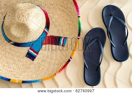 Постер, плакат: Straw Sombrero And Sandals On Beach Sand