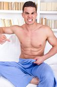 stock photo of genital  - handsome young half naked man having problems with impotence showing down with his finger - JPG