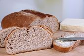 Rye bread with butter on table on bright background