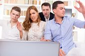 stock photo of pissed off  - young frustrated casual group of friends sitting on couch looking at laptop pissed off friends cheering on computer - JPG