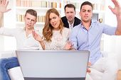 image of pissed off  - frustrated and shocked casual group of friends sitting on couch looking at laptop pissed off friends cheering on computer - JPG