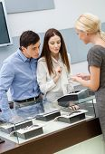 stock photo of jewel-case  - Shop assistant helps couple to select jewelry at jeweler - JPG