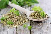 stock photo of oregano  - Oregano on a wooden spoon (against wooden background)