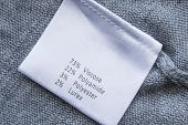 foto of lurex  - White label with fabric composition on gray cloth - JPG