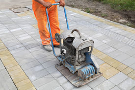stock photo of vibration plate  - Worker finishing concrete brick pavement with vibratory plate compactor - JPG