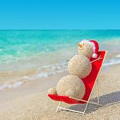 stock photo of beach hat  - Sandy snowman in red santa hat sunbathing in beach lounge - JPG