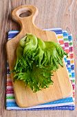 "stock photo of frilly  - Fresh green leaf lettuce ""frillis"" with water drops lie on a wooden cutting board