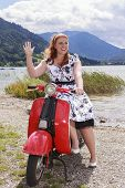 picture of vespa  - Young curvy redhead woman sitting on a scooter by the lake with a Petticoat Dress and waves - JPG