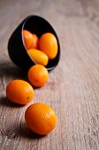 foto of kumquat  - Ripe kumquat orange lying on a wooden surface against the background of dishes filled with fruit - JPG