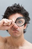 stock photo of mad scientist  - Curious man examining with a magnifying glass - JPG
