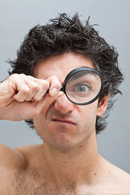 foto of mad scientist  - Curious man examining with a magnifying glass - JPG