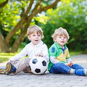 Постер, плакат: Two Little Sibling Boys Playing Soccer And Football