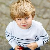 stock photo of strawberry blonde  - Funny little kid boy eating fresh organic strawberries in domestic garden on warm summer sunny day.