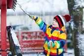 Постер, плакат: Little Boy In Colorful Winter Clothes Playing With Snowman Outdoors