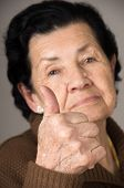 picture of grandma  - closeup portrait of grandma old woman holding thumb up over gray background selective focus - JPG