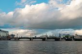 image of cloudy  - City bridge across the Neva River in Saint Petersburg in cloudy weather on a background of the cloudy sky - JPG