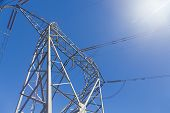 stock photo of electricity pylon  - Electricity pylon with high voltage power lines against blue sky - JPG