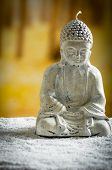 picture of garden sculpture  - closeup of small sculpture of buddha over white pebbles - JPG