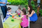 stock photo of father child  - A family picture of children having fun painting and decorating eggs outside. Children dye their Easter eggs as the mother and father watch and help at a crafts table together during the spring season in a beautiful garden setting. Part of a series.