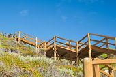 pic of guillotine  - wooden stairway from Guillotines beach to carpark orange ochre against blue sky over heathy scrub - JPG