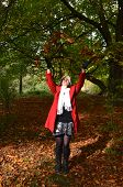 pic of throw up  - Girl throwing leaves up in the air in autumnal woods - JPG