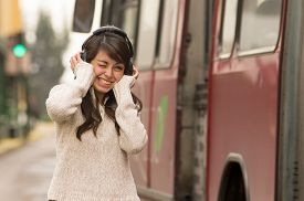 picture of noise pollution  - portrait of woman walking on the city street wearing headphones concept of noise pollution - JPG